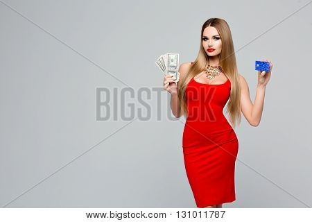 Beautiful fashionable woman holds the money and credit card. Stylish slender woman in a red dress with red lips, beautiful hair, necklace