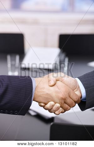 Closeup of hands. Businessmen shaking hands over table, in office meeting room.