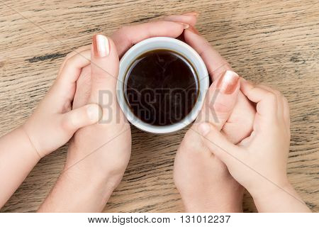 Women hands holding a cup of hot coffee in the children hands on an old vintage wooden table