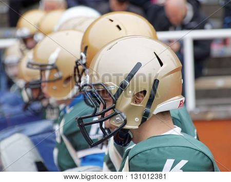 STOCKHOLM SWEDEN - MAY 14 2016: Football players wearing golden helmets they are the first obstarcle in the obstacle race Tough Viking Event in Sweden April 14 2016