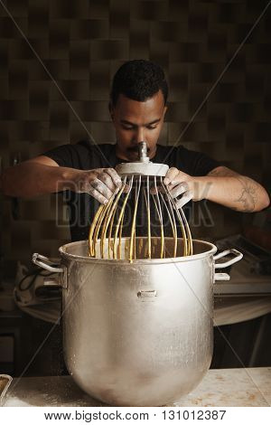 Professional Artisan Confectionery, Black Man Chief Takes Big Industrial Whisk From Big Pot With Ble
