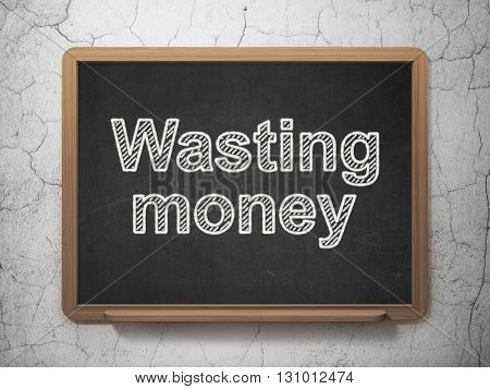 Money concept: text Wasting Money on Black chalkboard on grunge wall background, 3D rendering