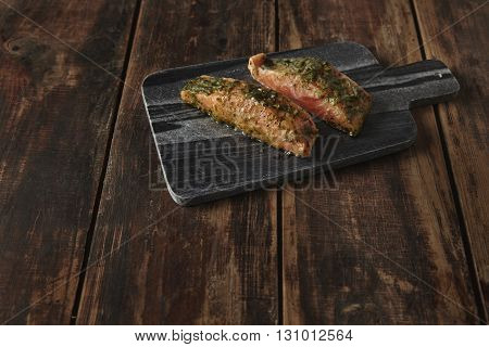 Two Raw Pieces Of Salmon In White Wine Sause With Spices And Herbs Presented On Stone Deck Prepared