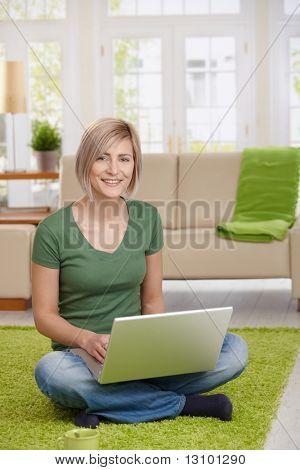 Glückliche Frau sitzt zu Hause im Erdgeschoss Wohnzimmer mit Laptop-Computer, Blick in die Kamera.
