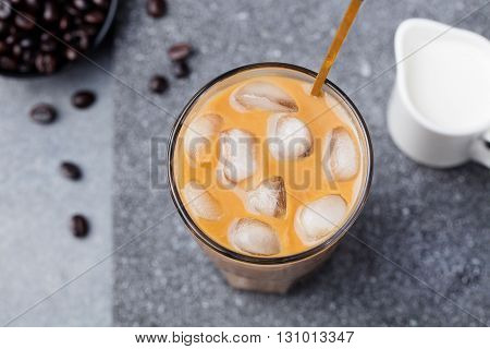 Ice coffee in a tall glass with cream and coffee beans on a grey stone background Top view Copy space
