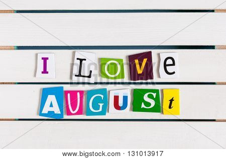 I Love August written with color magazine letter clippings on wooden board. Summer vacation concept, empty space for text.