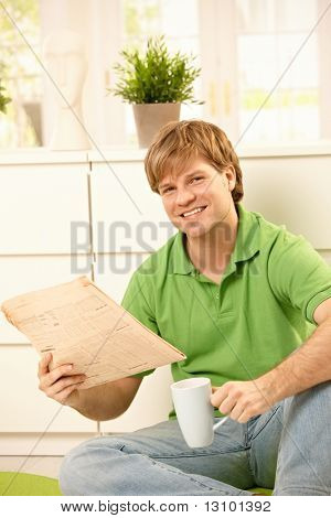 Handsome young man reading newspaper and drinking coffee, smiling  at camera at home.