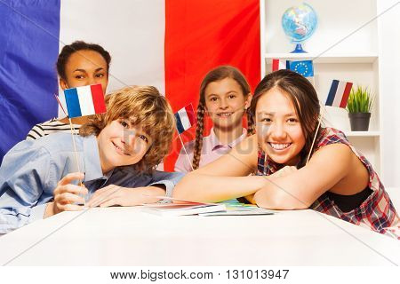 Portrait of four happy multiethnic teenage students holding flags of France at the class