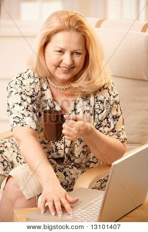 Senior woman drinking coffee, looking at laptop computer with big smile, typing.