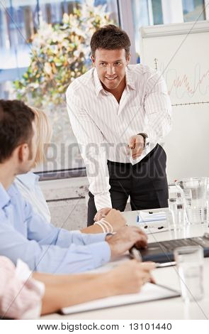 Businessman doing business presentation in meeting room, smiling.