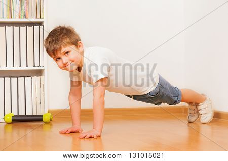 Smiling Caucasian preschooler boy making gymnastics, doing push-ups, at the children's room