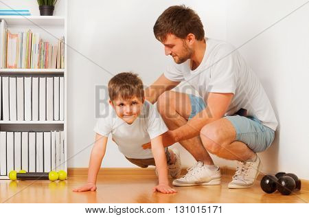 Father teaching his kid son doing exercises, pushing ups or pressing ups at the room