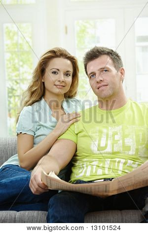 Love couple reading newspaper together on couch at home, looking at camera, smiling.