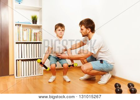 Cheerful father teaching kid son to squats with dumbbells at home