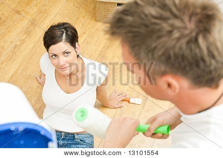 Schöne Frau sitzen auf Boden blickte zu Mann arbeiten mit Farbroller Pinsel halten.