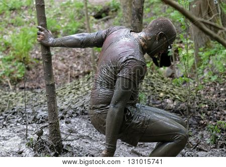 STOCKHOLM SWEDEN - MAY 14 2016: Man covered with mud leaning on a tree in the obstacle race Tough Viking Event in Sweden April 14 2016