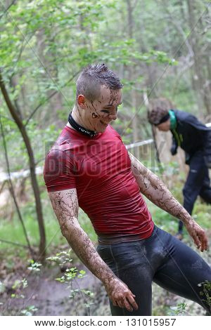 STOCKHOLM SWEDEN - MAY 14 2016: Smiling muscular standing man in red shirt covered with mud in the obstacle race Tough Viking Event in Sweden April 14 2016