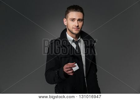 Handsome young businessman in black coat, white shirt and tie giving blank business card over grey background