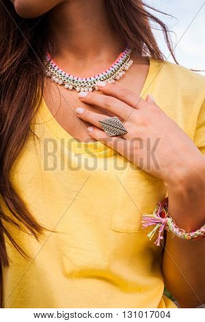 female  hand and neck  with large ring and colorful necklace closeup outdoor shot