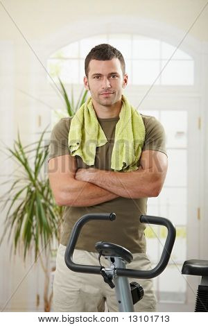 Personal trainer wearing sportswear and towel standing in living room at home with training bike, smiling.