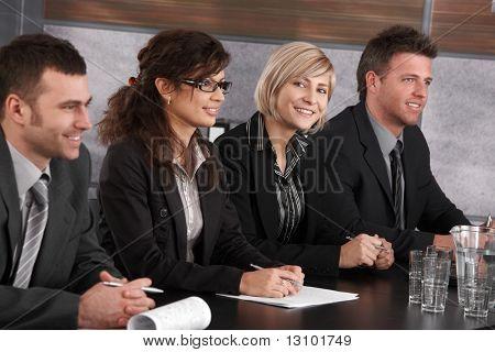 Atractiva joven empresaria sentado en la mesa en el seminario de negocios con colegas, buscando