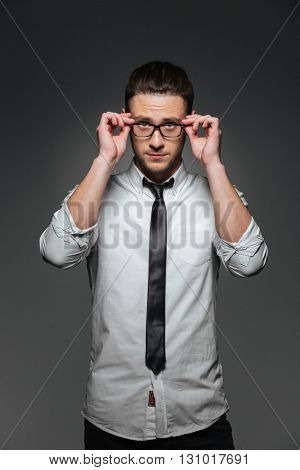 Portrait of confident young businessman in white shirt, tie and glasses over grey background
