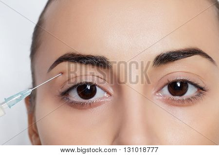 Attractive young woman gets cosmetic injection isolated over white background. Doctors hands making an injection in face. Beauty Treatment.