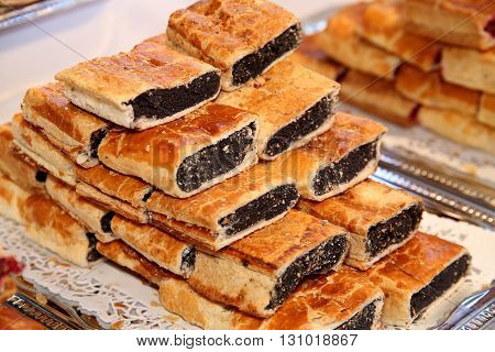 Strudel with poppy seeds on plate at rural retail market
