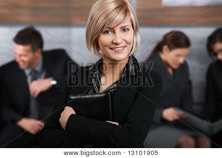 Portrait of mid-adult businesswoman looking at camera, smiling, business people in background.