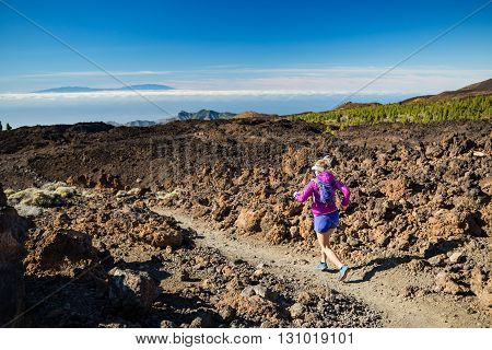 Young woman running in mountains on sunny summer day. Beauty female runner jogging and exercising outdoors in nature trail running training on rocky trail footpath on Tenerife Canary Islands