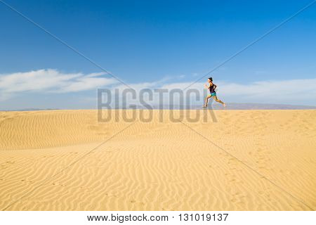 Woman barefoot running training on beautiful inspirational desert dunes or beach on sunny summer day. Beauty female runner jogging and exercising in nature Gran Canaria Canary Islands.