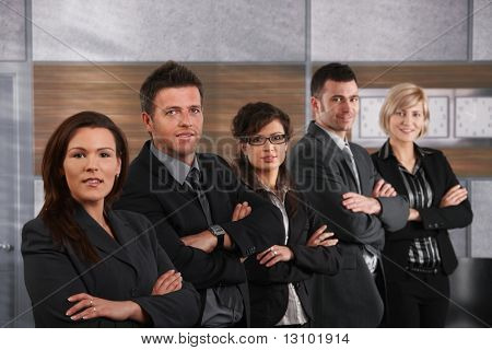 Portrait of business people standing in a row on office corridor, looking at camera.