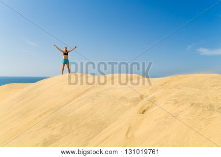 Fitness successful happy woman with arms up outstretched celebrating on beautiful inspirational beach dunes on summer day. Beauty female runner training and exercising outdoors business concept.