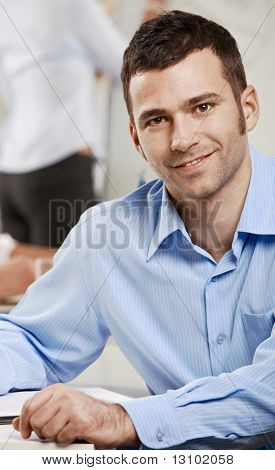 Happy businessman sitting at table in meeting room, looking at camera, smiling.