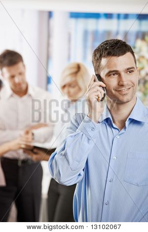 Portrait of smiling businessman talking on mobile phone in office.