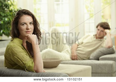 Young couple resting at home lying o couch. Selective focus on woman.