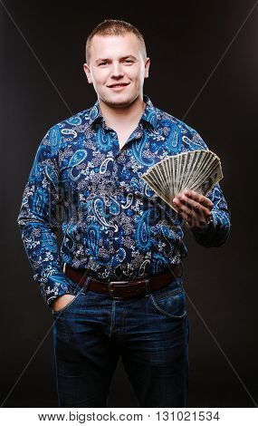 Portrait of a man in a shirt and jeans holds a lot of hundred dollar bills. The guy is holding a salary, money