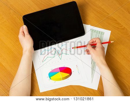 Digital tablet and pencil in female hands on a background of the desktop.