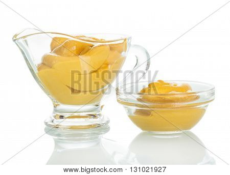 Mustard in a glass bowl and a gravy boat isolated on white background.