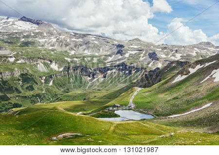 Idyllic summer view with clear mountain lake and mountain peaks in snow in Austria Alps