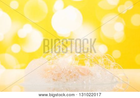Soap with foam in the bathroom on an abstract yellow background.