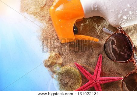 Sunscreen Spray And Sunglasses On Sand In Table Top View