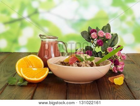 Healthy breakfast. A jug of juice, a bowl of oatmeal and orange on abstract green background.
