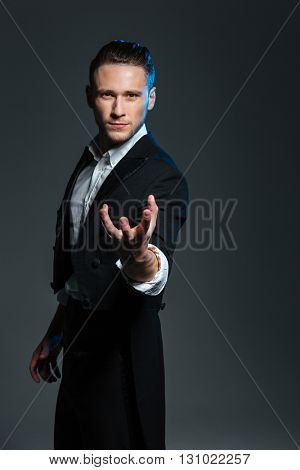 Attractive mysterious young magician holding something on palm over grey background