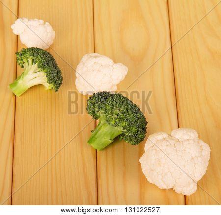 Fresh broccoli and cauliflower on a background of light wood.