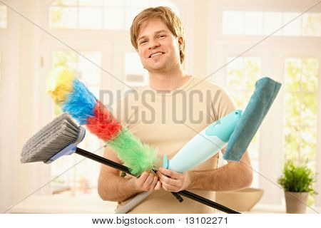 Young man smiling confidently with cleaning tools, holding mop, broom and flannel.