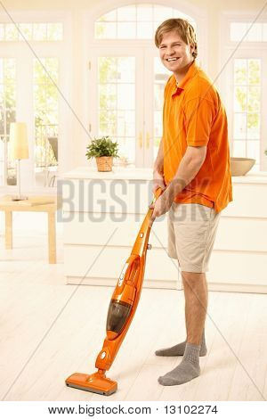 Portrait of happy guy holding hoover standing in living room, smiling at camera.