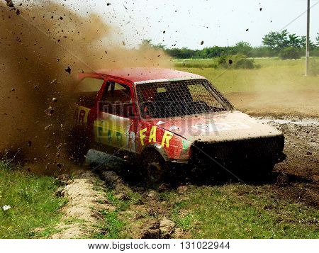 Novi Sad, Serbia - May 22, 2004: Rally car in fast driving sprays mud on a dirty rally road during race