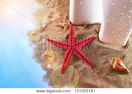 Two Sunscreen On Sand With Starfish And Shell On Table