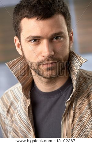 Closeup portrait of handsome trendy young man looking at camera.